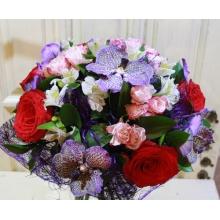 Букет из красных роз, темно-синих цветов орхидеи Ванды, кустовой розы, альстромерии в натуральной упаковке из сизаля с лентой.