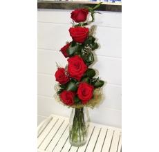 Вертикальный букет из 7 красных роз, драцены, листьев аспидистры, брунии, зелени в натуральной упаковке из сизаля с лентой.