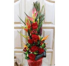 Букет из экзотической геликонии, красных роз, альстромерии, гиперикума, зелени в натуральной упаковке из сизаля.