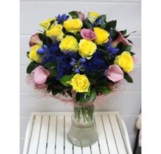 Букет из ярко-желтых роз, розовых калл, джентианы, волокон сизаля на техническом каркасе с зеленью в натуральной упаковке с лентами.