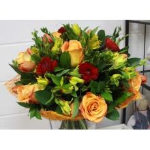 Букет из сортовых оранжевых роз, тюльпанов, красных ранункулюсов, желтой альстромерии, самшита, салала и другой зелени в натуральной упаковке с лентами.