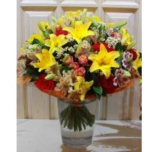 Большой букет из желтой лилии, красных роз, кустовой розы, альстромерии, матрикарии, зелени в натуральной упаковке с лентами.