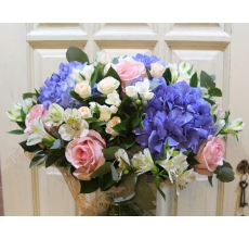 Большой букет из голубой гортензии, нежно-розовых роз, фрезии, альстромерии, кустовой розы, зелени, эвкалипта в натуральной упаковке с лентами.