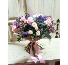 Букет из лиловых орхидей, персиковой гвоздики, белой кустовой розы, персиковой розы, статицы, восковника, эвкалипта, другой экзотической зелени в упаковке из бумаги крафт с атласной лентой.