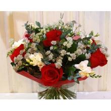Букет из красных роз, белой фрезии, белой астранции, зелени в упаковке из фетра с лентами.
