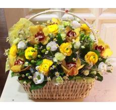 Корзина из теплых желтых цветов орхидеи, ранункулюсов, матрикарии, белой эутомы, кустовой фисташковой гвоздики, гиперикума, зелени с бантом и букашечками - божьими коровками.