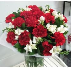 Букет из цветов фрезии, красной гвоздики (25 шт) с зеленью в натуральной упаковке с атласными лентами.