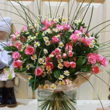 Букет из 11 веток кустовой розы с матрикарией и зеленью в натуральной упаковке с лентами.