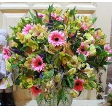 Букет из мини-гербер, орхидей, кустовой гвоздики фисташкового цвета, альстромерии, синей вероники, зелени, сизаля с натуральной упаковке с лентами. Диаметр 55-60 см.