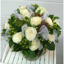 Букет из 11 крупных белых роз, 16 веток гиперикума, асклепии, зелени с капроновыми белыми бантами в натуральной упаковке из сизаля с лентами.