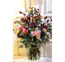 Высокий открытый букет из экзотического темно-бордового бархатного анигозантоса, персиковой кустовой розы, оранжевой кустовой гвоздики, сортовой персиковой гвоздики, роз, эвкалипта, салала с бантом из атласной ленты.