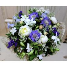Букет летних цветов из пионов, скабиозы, дендробиума, дельфиниума, кустовой розы, статицы, альстромерии, зелени в натуральной упаковке с лентами.
