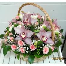 Круглая корзина из цветов орхидеи, кустовой розы, фрезии, гипсофиллы, зелени с атласным бантом.