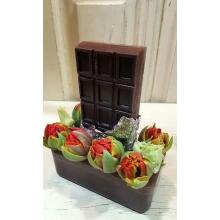 Свеча ручной работы в форме шоколада с подставкой из парафина и красными тюльпанами.