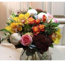 Яркий букет из сортовых хризантем, орхидей, крупных роз, кустовой розы, седума, альстромерии, восковника, зелени с упаковкой из бумаги крафт с лентой.