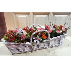 Вытянутая плетеная корзина с ручками. (длина 45 см, ширина 15 см) Состав: ятрофа, кустовые розы (белые, оранжевые, розовые), клематис, гиперикум, экзотическая зелень, лимониум, лаванда.