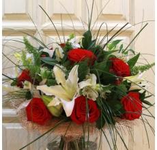 Большой букет из крупной лилии сорта Сибирия, крупной красной розы, альстромерии, экзотической зелени в натуральной упаковке с лентами.