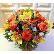 Яркий букет из крупных оранжевых роз, оранжевых кустовых роз, орхидей, альстромерии, зелени в натуральной упаковке из сизаля с лентами.