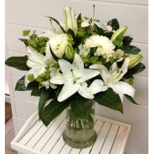 Букет из белой лилии, хризантемы, альстромерии, зелени в натуральной упаковке с лентами
