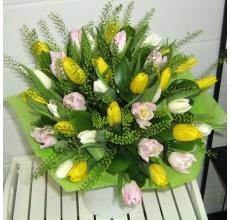 Разноцветные тюльпаны с зеленью грин белл в натуральной упаковке с лентой.