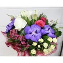Букет из белого амариллиса, малиновых роз, орхидеи ванды, статицы, кустовой розы, альстромерии, зелени в натуральной упаковке с лентами.