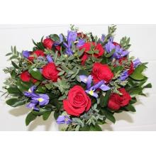 Большой яркий букет из красных роз, синих ирисов, эвкалипта, зелени в натуральной яркой упаковке с лентами