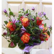 Букет из фиолетово-сиреневого клематиса, оранжевых роз, зелени в упаковке с атласными лентами.