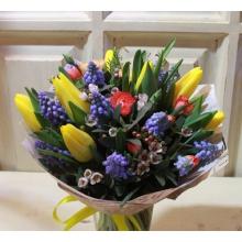 Небольшой весенний букет из 7 желтых тюльпанов, мускари, кустовой гвоздики, восковника, зелени в упаковке из бумаги крафт с бантом.