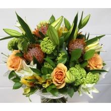 Букет из персиковых роз, левкоспермума, калины, альстромерии, зелени в натуральной упаковке с лентами