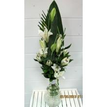 Вертикальный букет из 3 белых лилий, листа стрелиции, стилграса, зелени с широкой лентой и декоративными булавками