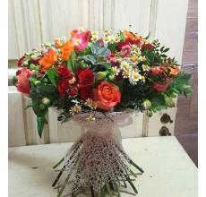 Яркий романтический букет из роз, кустовых роз, антириниума, альстромерии, матрикарии, зелени в натуральной кружевной упаковке с атласной лентой.