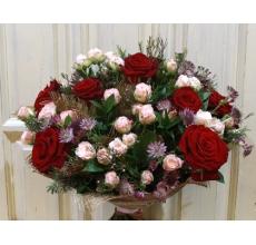 Букет из красных роз сорта гран-при, кустовой розы сорта яна, астранции, восковника, зелени с вставками из рогожи, в натуральной упаковке с лентами.