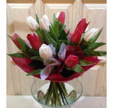 Букет из 15 красных и белых тюльпанов с зеленью и разноцветными флажками в упаковке из фетра с бантом.