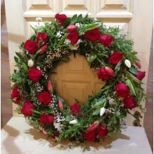 Траурный венок из красных роз, веток спиреи, красных и белых тюльпанов, зелени, гипсофиллы. Диаметр 60 см - 70 см.