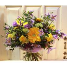 Большой букет из фиолетовых клематисов, желтых роз, гербер, гиперикума, фисташковой кустовой гвоздики, фиолетовой эустомы, зелени в разноцветной упаковке с лентами