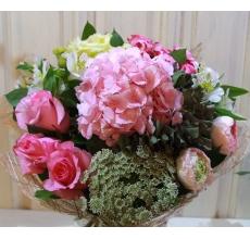 Букет из розовой гортензии, розовых сортовых роз, кустовой розы, крупных ранункулюсов, альстромерии, амми, зелени в натуральной упаковке из сизаля с бантом.