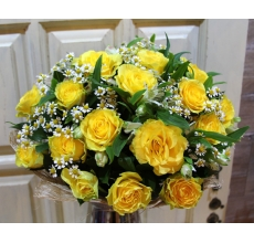 Букет из 25 желтых роз с матрикарией, белой альстромерией и зеленью в натуральной упаковке с лентами.