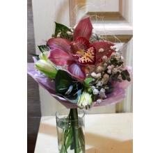 Мини-букет из розовой орхидеи, альстромерии, гипсофиллы, зелени в упаковке из фетра с лентами.