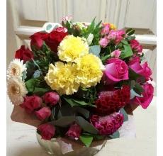 Букет из ярко-малиновых роз, красных роз, малиновой кустовой розы, разноцветной целлозии, бархатных гербер, сортовой лимонной гвоздики, кустовой гвоздики, зелени в упаковке из бумаги крафт.