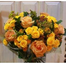Теплый букет из оранжевых роз, кустовых роз, ягод калины, зелени в натуральной упаковке с лентами.