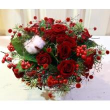 Небольшой европейский букет из кустовой красной розы, стиллингии, хлопка, ягод илекса, веток пихты, салала с атласным бантом. Диаметр 25 см.