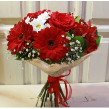 Небольшой яркий букет из красных гребер, красных роз, гипсофиллы, альстромерии, кустовой хризантемы, зелени в натуральной упаковке с большим бантом.