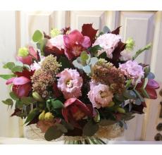 Лилово-бордовый букет из темной орхидеи цимбидиум, розового седума, альстромерии, эустомы, дубовых листьев, зелени в натуральной упаковке из сизаля с лентами.