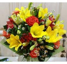 Летний букет из желтой лилии (азиатки, не имеет яркого запаха), оранжевых роз, матрикарии, альстромерий с зеленью в натуральной упаковке с лентами.