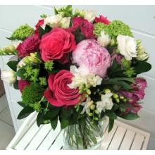 Букет из розовых пионов, малиновых крупных роз, кустовых роз, трахелиума, калины, эустомы, фрезии, альстромерии, буплерума с зеленью и атласными лентами