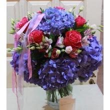 Большой праздничный букет в виде ярусного торта из 7 голубых гортензий, малиновых сортовых роз, эустомы, альстромерии, зелени с разноцветными лентами в виде акцента.