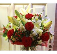 Большой букет из лилий, красных роз, гиперикума, альстромерии, статицы, зелени в натуральной упаковке из сизаля с лентами.