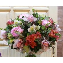 Букет из розовых пионов, орхидей, альстромерии, тиландсии, зелени в натуральной упаковке с лентами.