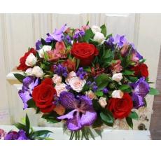 Большой праздничный букет из красных роз, синих орхидей сорта Ванда, альстромерий, статицы, персиковых роз, зелени в натуральной упаковке из сизаля с лентами.
