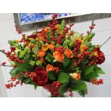Букет в теплых тонах из красных роз, оранжевых кустовых роз, илекса, орнитогалума, буплерума, зелени в натуральной паковке из сизаля с лентами.